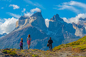 Three tourists during a hiking adventure inside Torres del Paine national park, looking upon the Andes peaks of Cuernos del Paine, Patagonia, Chile.
