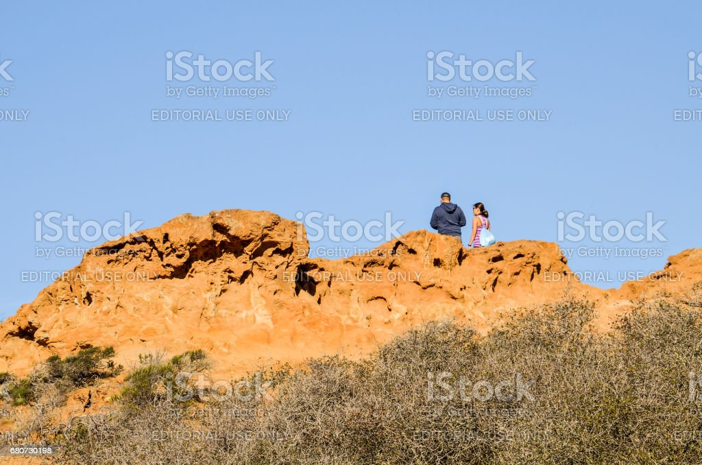 Torrey Pines cliff in pacific ocean in San Diego California with people standing on top on trail stock photo