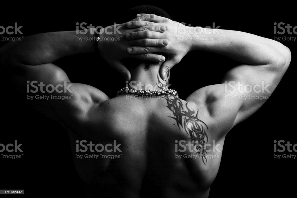 Torso of a muscular man with tribal tattoo near shoulder stock photo