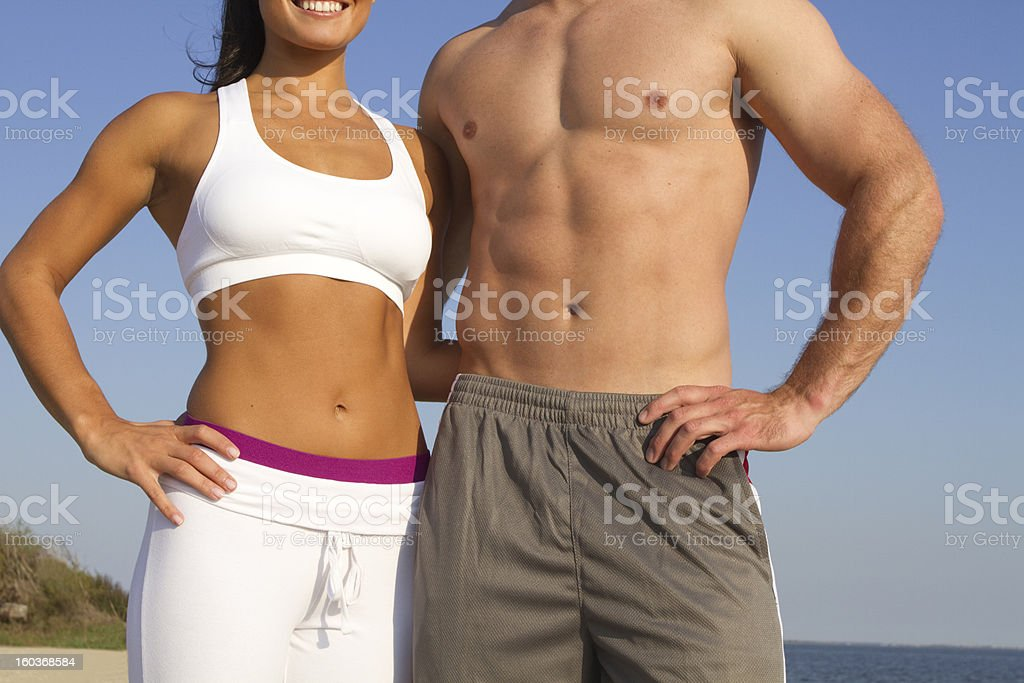 torso of fit couple at the beach stock photo