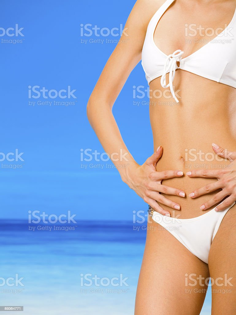 Torso di giovane splendida conciata donna in bikini sulla spiaggia foto stock royalty-free