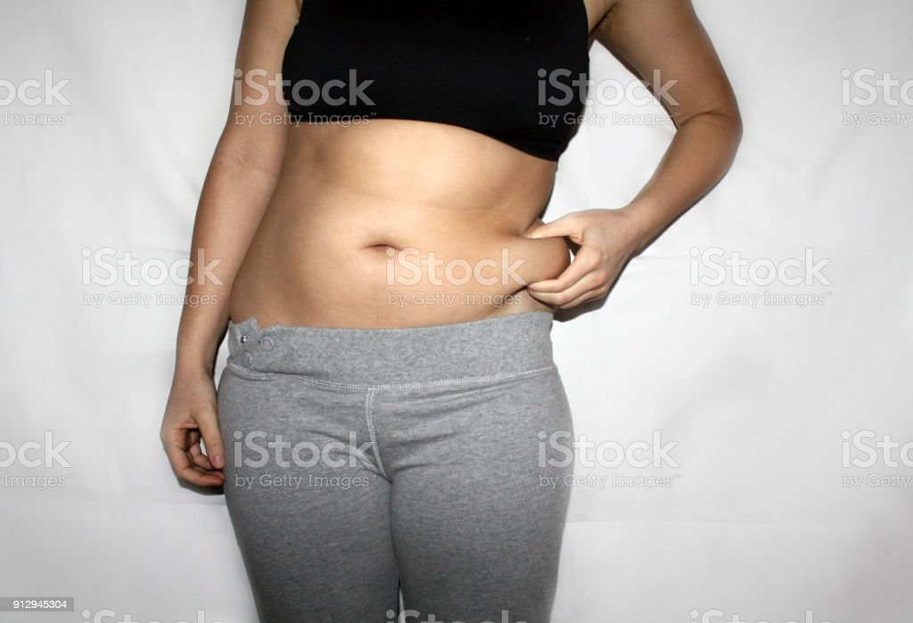 Torso of young woman, which holding a belly fat in fingers. Overweight, weight loss, christmass food kilograms, dissatisfaction with own body concept. stock photo