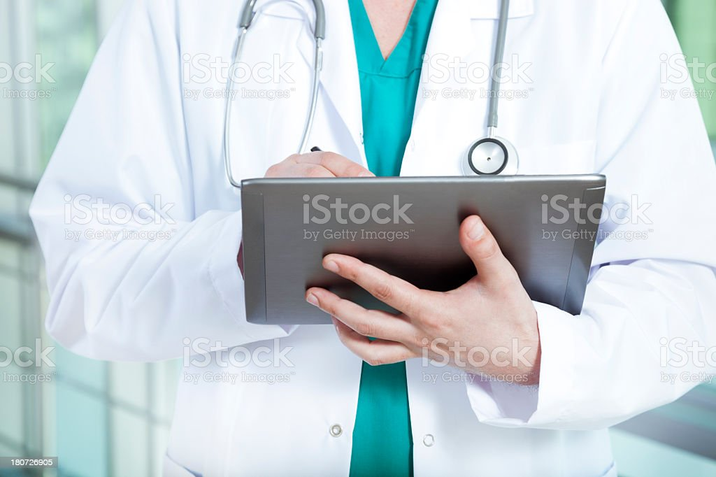 Torso view of a doctor consulting a tablet computer royalty-free stock photo