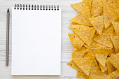 istock Tortilla chips with blank notebook on white wooden table, top view. Mexican food. Flat lay, from above, overhead. Space for text. 1020181768