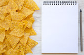 istock Tortilla chips with blank notepad on white wooden table, top view. Mexican food. Flat lay, from above, overhead. Space for text. 1018997390