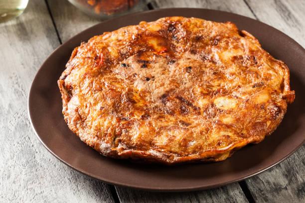 tortilla de patatas. kartoffel-tortilla mit chorizo wurst, kartoffeln, paprika und ei, begleitet von olivenöl - kartoffel frittata stock-fotos und bilder