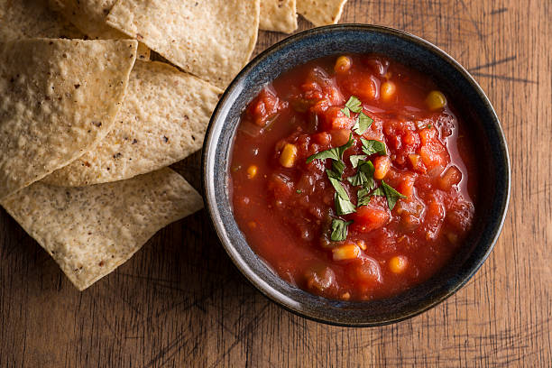 Salsa Tortilla Fresh Salsa with Tortilla Chips on a rustic wooden background salsa sauce stock pictures, royalty-free photos & images