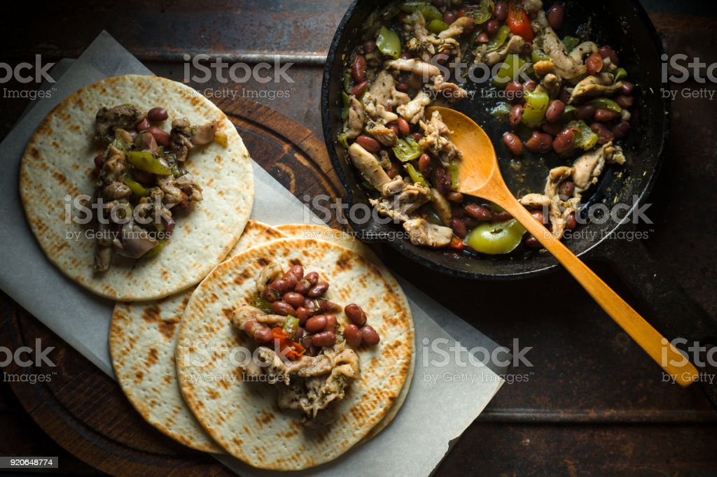 Tortilla with filling on parchment and frying pan on table stock photo
