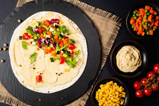 tortilla mit gemüse und hummus mit kichererbsen - veggie wraps stock-fotos und bilder