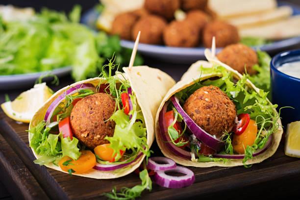 Tortilla mit Falafel und frischem Salat umhacken. Vegane Tacos. Vegetarisch gesundes Essen. – Foto