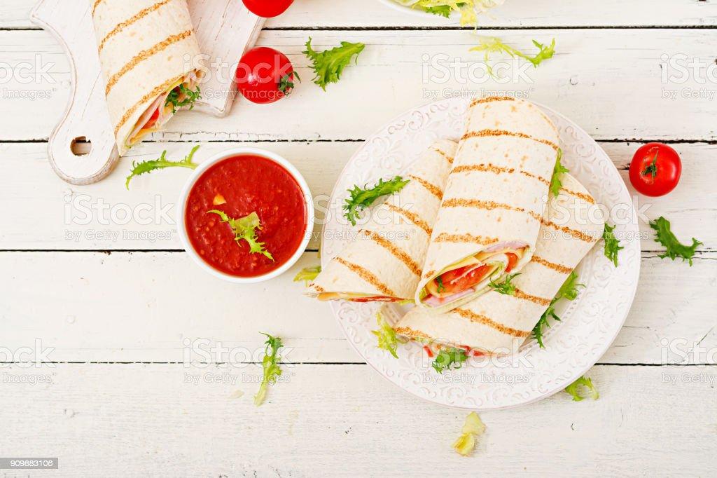 Tortilla-Wrap mit Schinken, Käse und Tomaten auf einem weißen Hintergrund aus Holz. Ansicht von oben – Foto
