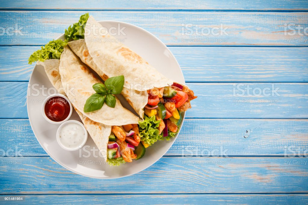 Tortilla wrap with meat and vegetables stock photo