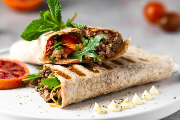 토르티야는 신선한 채소, 다진 고기, 블러드 오렌지로 샌드위치를 포장합니다. 부리토, 샌드위치 랩, 파히타 랩 - 주요리 뉴스 사진 이미지
