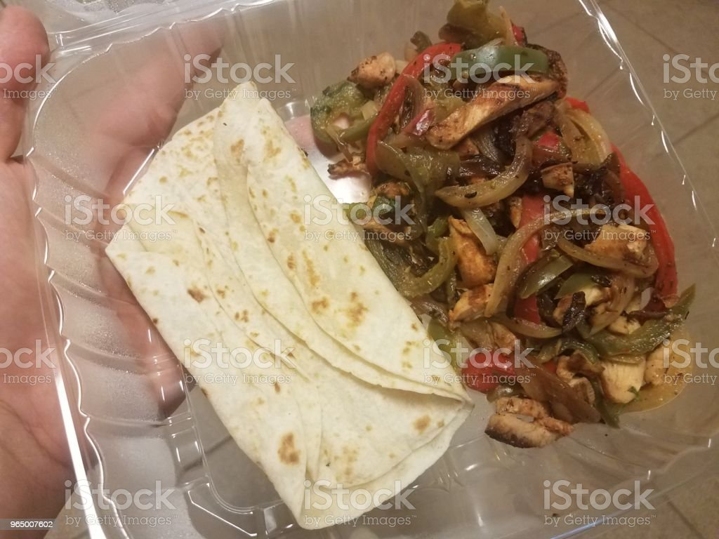tortillas, chicken, and vegetables in plastic container stock photo