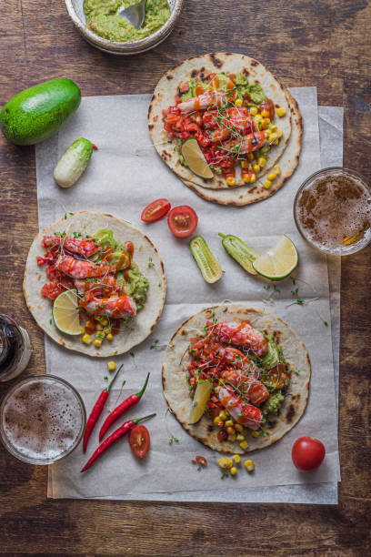 Tortillas with crab meat, guacamole, salad and salsa, two glasses of bee, flat lay stock photo