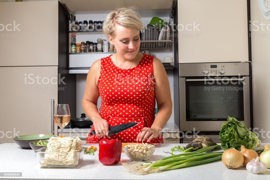 Tortoise eating salad while girl looks at him and cuts carrot stock photo