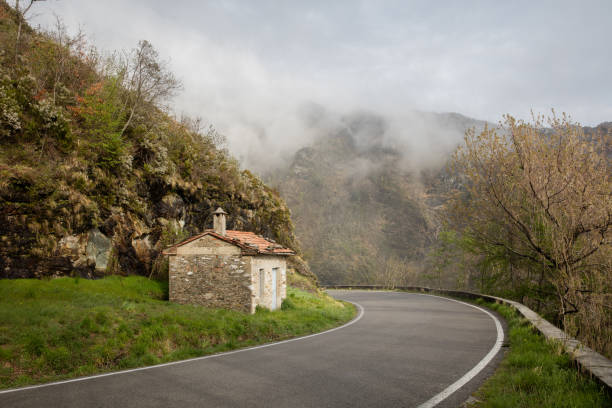 Toscany in the mist, a road going around the bend towards the mist stock photo