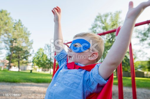 Cute little three year old boy dressed in a blue mask and red superhero cape holding his arms up as he plays pretend in a playground at a local park on a warm summer day. He is smiling and wearing a blue button up shirt.