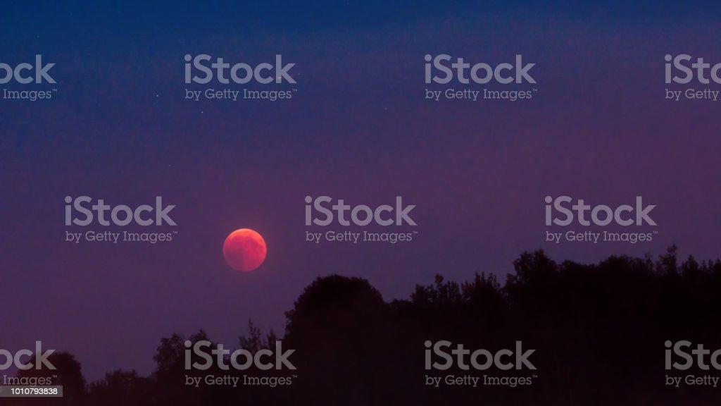 Totale Mondfinsternis 2018, Juli Blutmond und Sterne über Wald – Foto