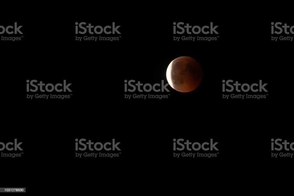 Moon in the starry sky with a blood red color as a result of a lunar...