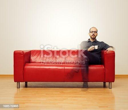 Relaxed man having a coffee on a sofa and becoming invisible. Relaxation concept.
