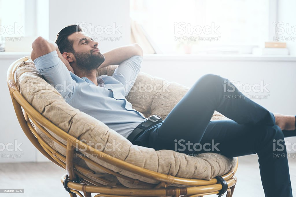 Total relaxation. Handsome young man keeping eyes closed and holding hands behind head while sitting in big comfortable chair at home 1920-1929 Stock Photo