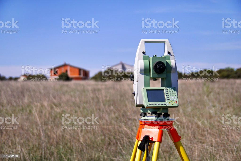 Total station. Survey Instrument geodetic device. Fall time land surveying, set in field. Modern surveyor equipment, used in surveying and building construction for measurement, at construction site. royalty-free stock photo