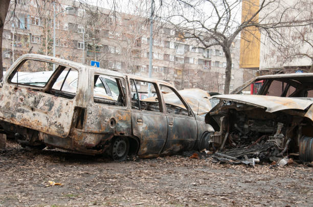 Totally destroyed and damaged cars burned in fire in the war zone or in civil demonstrations close up stock photo