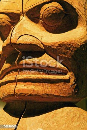 old cedar totem pole in close-up, vertical frame