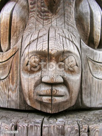 Close-up view of a totem pole carving. Shallow depth of field, focus on face.