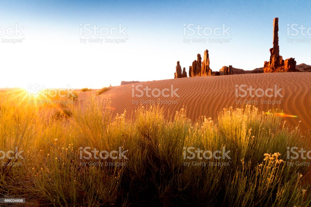 Totem Pole with rippled sand dunes at sunrise, Monument Valley, Arizona, USA stock photo