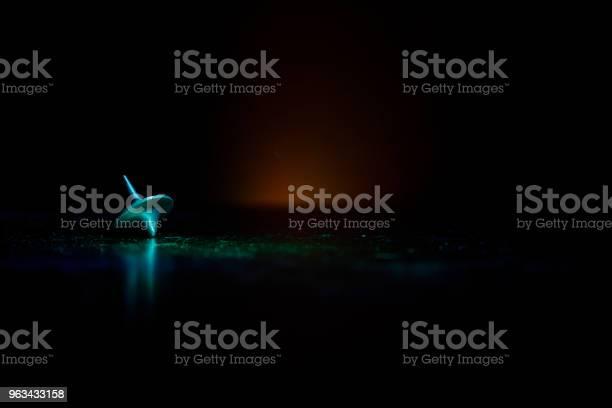 Totem Przędzenia Góry Przędzenia Chwiejny I Zatrzymując Się Spinning Top Na Powierzchni Lustra Z Stonowanych Dymu Światła Tła Whirligig W Akcji W Ciemnym Pokoju Na Stole - zdjęcia stockowe i więcej obrazów Fotografika