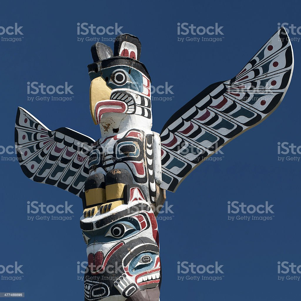 Totem wood pole in the blue cloudy background stock photo