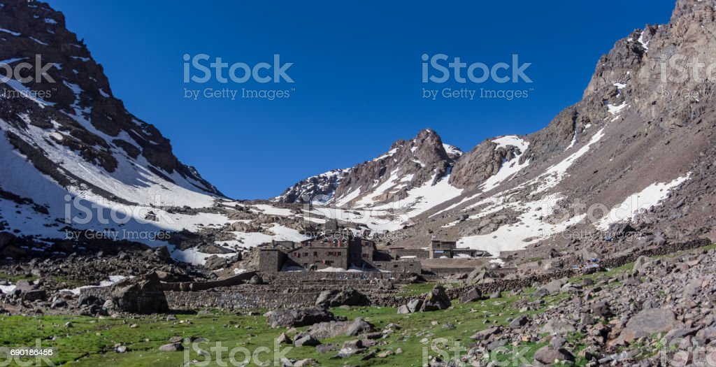 Toubkal national park in springtime with mount, cover by snow and ice, Refuge Toubkal, start point for hike to Jebel Toubkal, – highest peak of Atlas mountains and Morocco stock photo