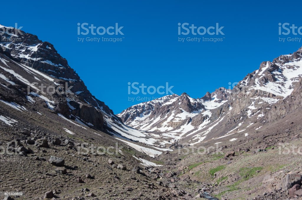 Toubkal national park in springtime with mount, cover by snow and ice, valley near Refuge Toubkal, start point for hike to Jebel Toubkal, – highest peak of Atlas mountains and Morocco stock photo