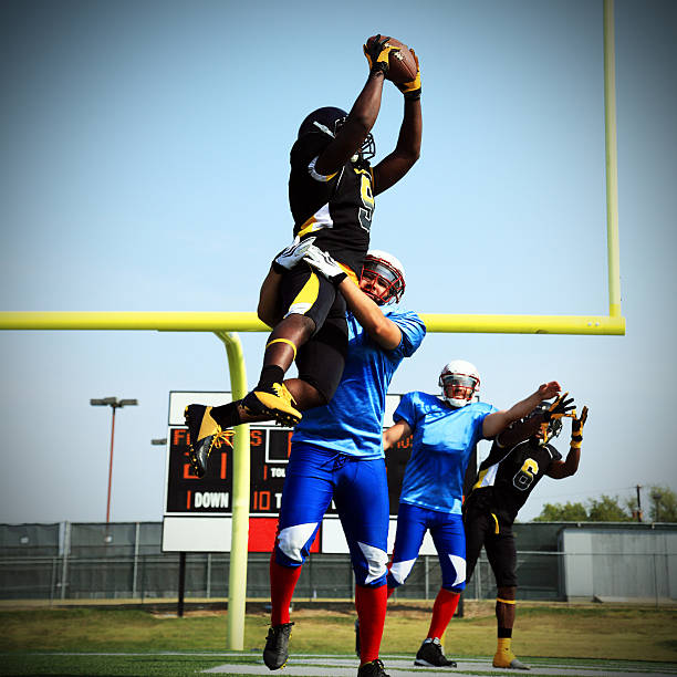 Touchdown Catch A wide receiver jumps and catches a touchdown pass! wide receiver athlete stock pictures, royalty-free photos & images