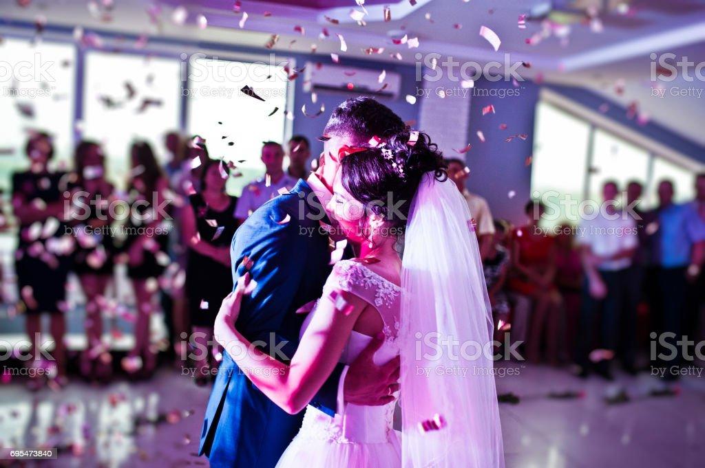 感人和情緒第一次跳舞的這對夫婦在他們的婚禮了五彩紙屑和彩燈的背景上。圖像檔