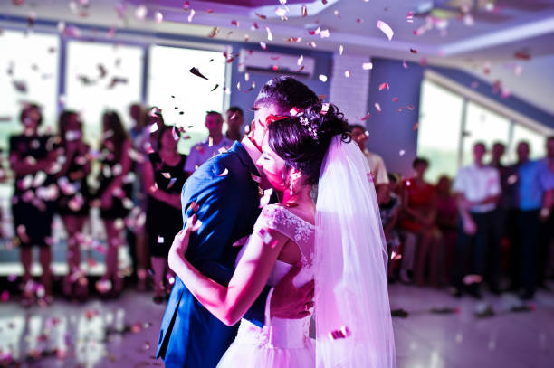 Touching and emotional first dance of the couple on their wedding with confetti and colorful lights on the background. stock photo