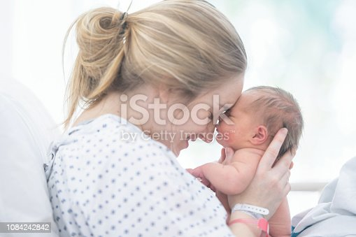 A mother is touching foreheads with her newborn daughter. They are laying in a hospital bed.