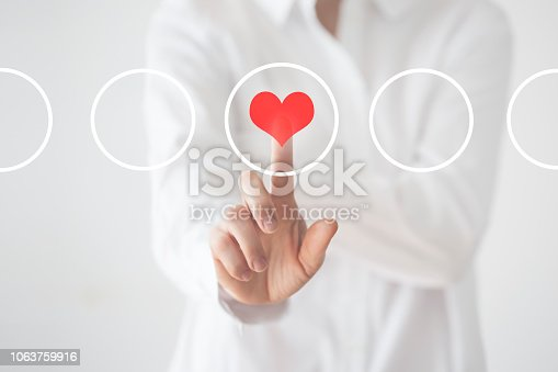 Woman touching heart icon.