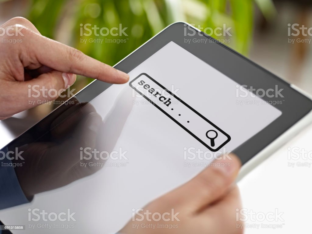 touching search bar on a tablet computer stock photo