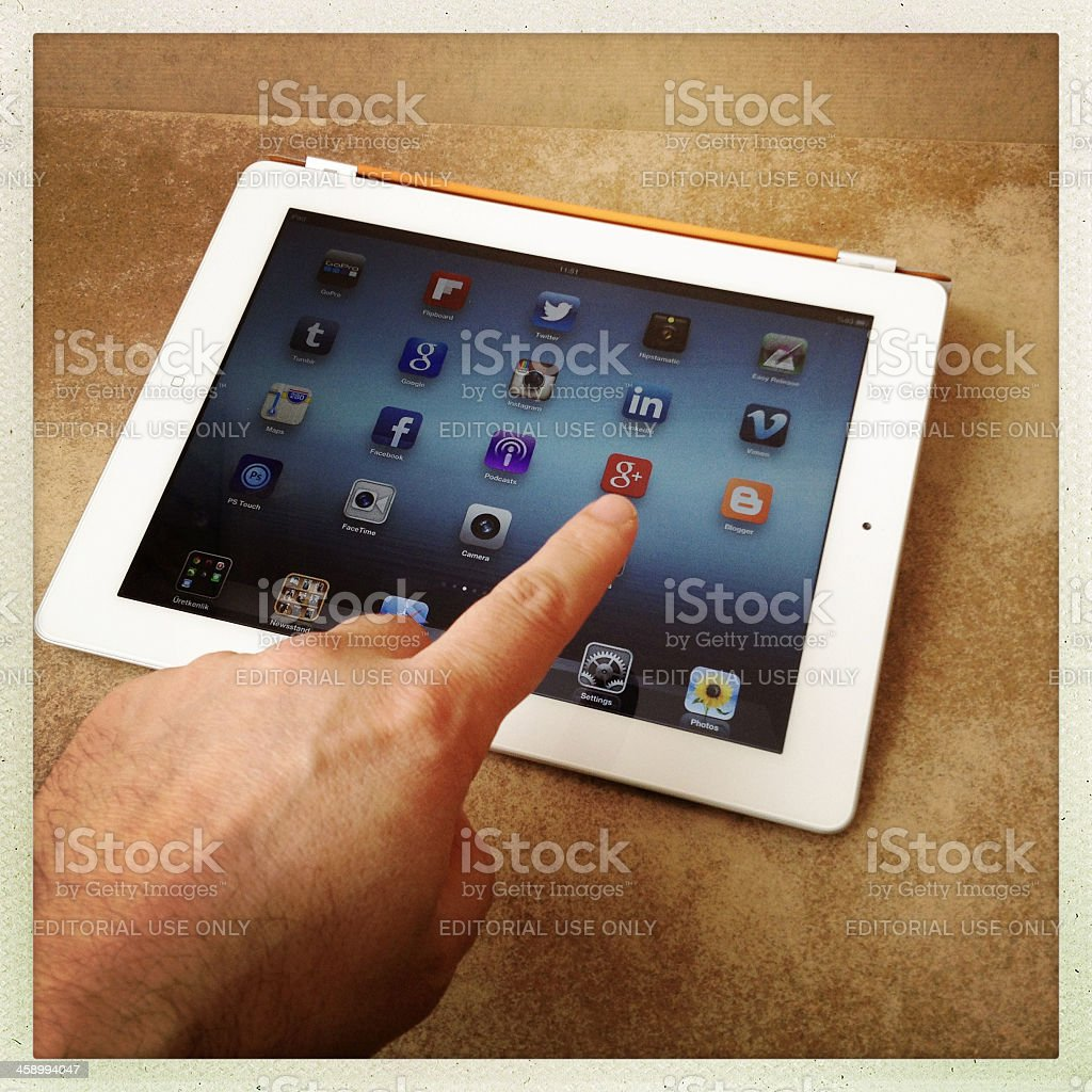 Touching the Google Plus  icon on iPad screen stock photo