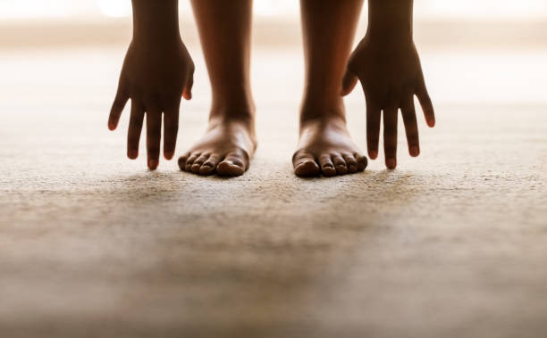 Touching the ground Low section view of feet of woman bending down with hands touching the floor touching toes stock pictures, royalty-free photos & images