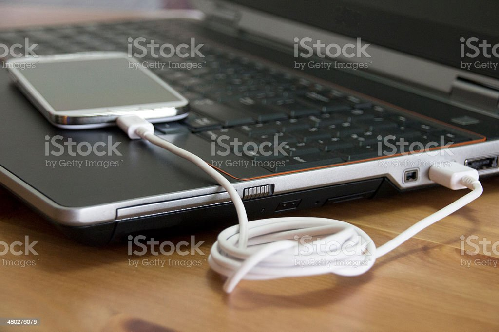 Touchscreen phone charged by a laptop computer stock photo