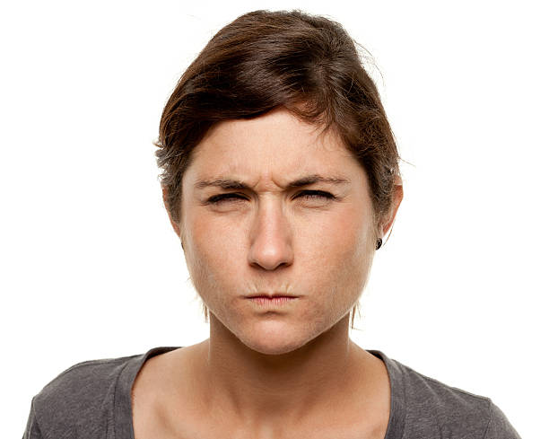 tough frowning young woman close up portrait - frowning stock photos and pictures