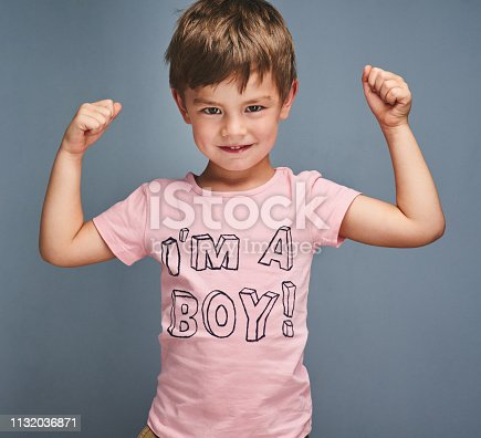 """Studio portrait of a cheering boy wearing a shirt with """"I'm a boy"""" printed on it against a grey background"""