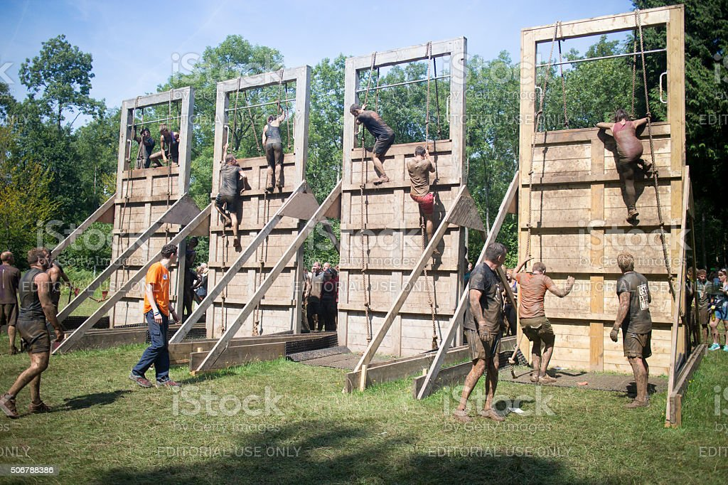 Tough Mudder competitors taking on a set of tall barriers stock photo