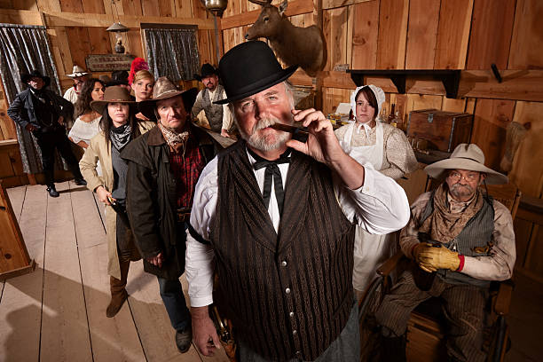 Tough Saloon Boss with Customers Big saloon owner with cigar and customers behind him saloon stock pictures, royalty-free photos & images