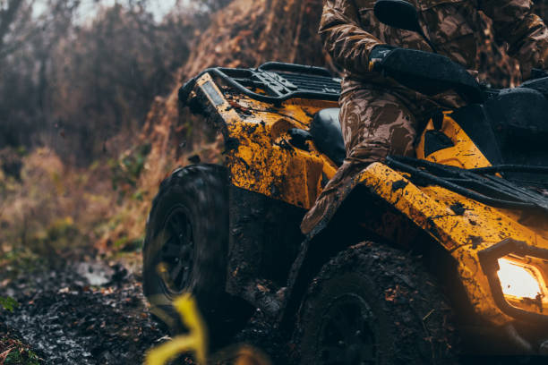 Tough terrain for a tough man Close up of man driving fix quad on a muddy path quadbike stock pictures, royalty-free photos & images