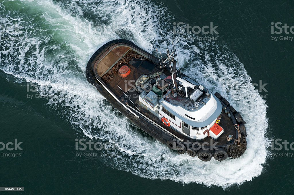 Tough tugboat plows through ocean stock photo